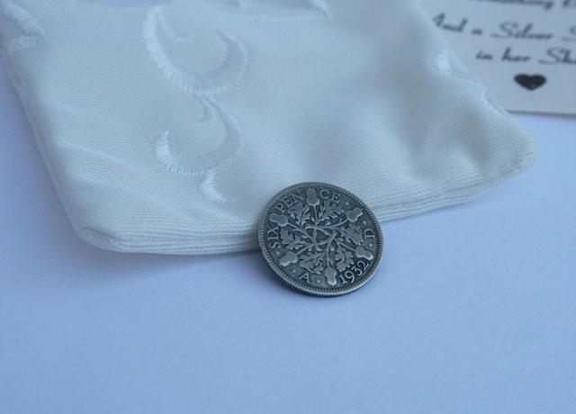 zilveren sixpence uit 1932, in handgemaakt ivoorkleurig zakje