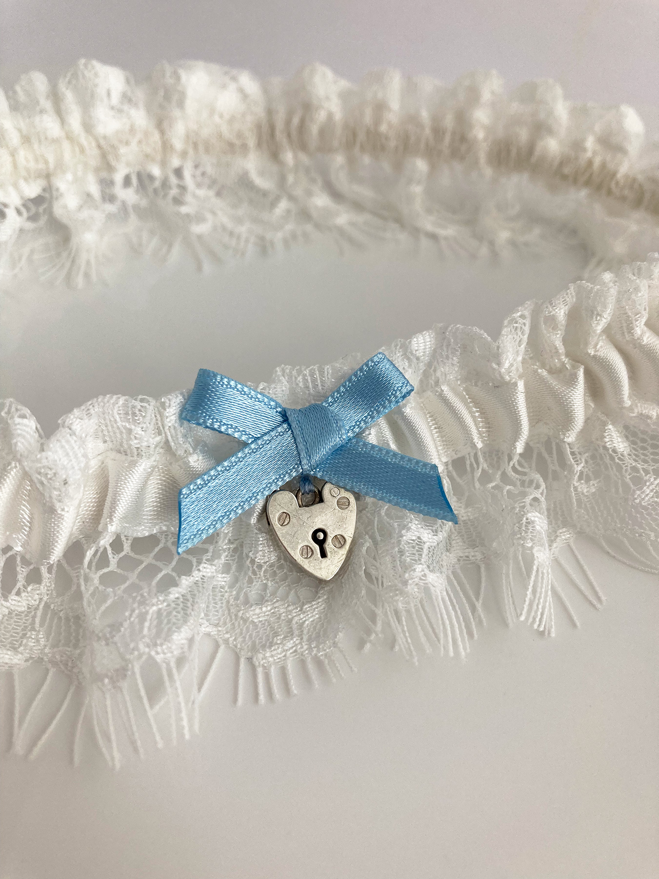 Offwhite kousenband met zilveren hart slotje